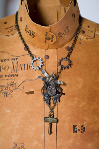 Image of steampunk necklace with a key and fly cog wheels hanging on a decorative bust by Jennifer Campbell
